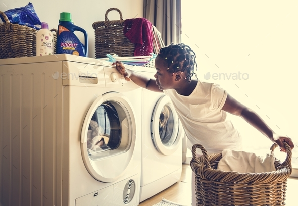 Young teen girl washing clothes using washing machine - Stock Photo - Images