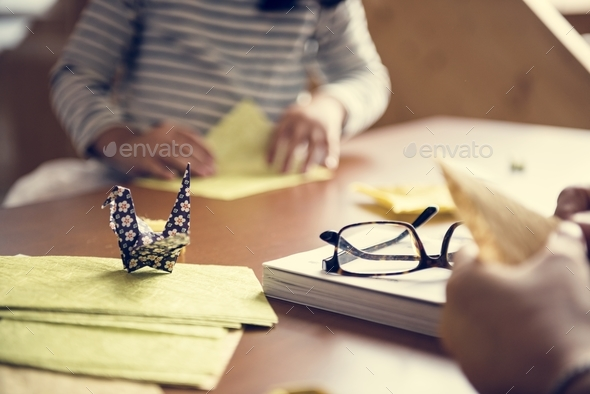 Hands making swan origami on wooden table - Stock Photo - Images