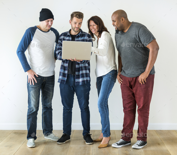 Group of diverse friends using laptop together - Stock Photo - Images