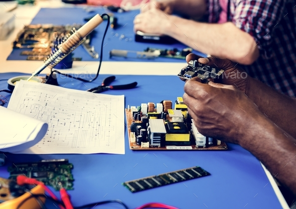 Side view of technician working on computer mainboard - Stock Photo - Images