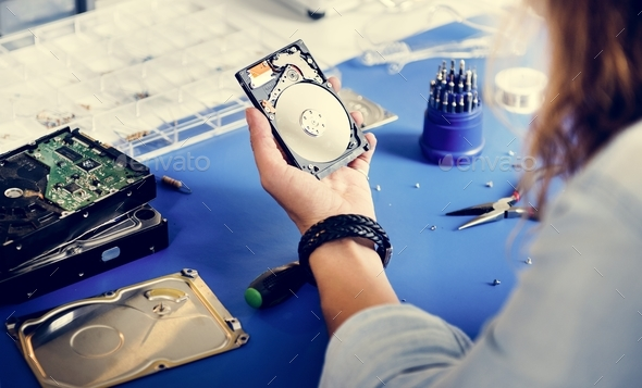 Technician holding HDD fixing at electronic repair shop - Stock Photo - Images