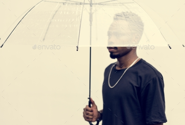 African man using an umbrella - Stock Photo - Images