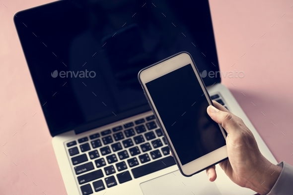 Hand holding smartphone and laptop in background - Stock Photo - Images