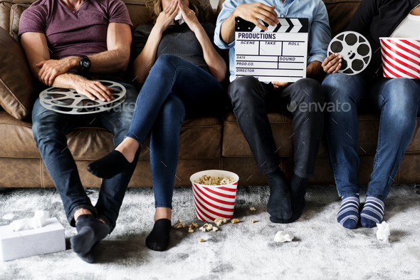 Group of friends holding movie and film objects - Stock Photo - Images