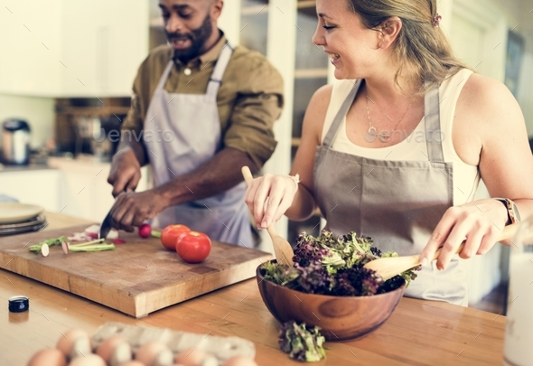A couple is cooking in the kitchen together - Stock Photo - Images