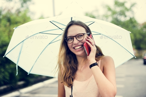 A woman using a mobile phone under an umbrella - Stock Photo - Images