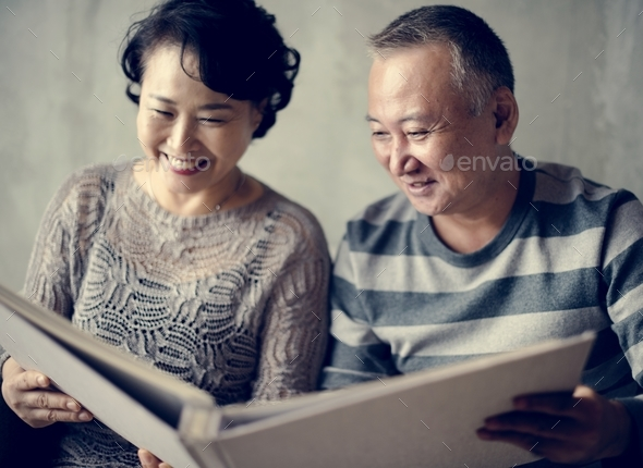 Asian senior couple sitting together at sofa - Stock Photo - Images