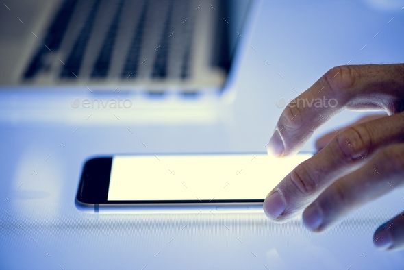 Hand using smartphone with laptop on the side - Stock Photo - Images