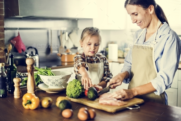 daughter helping mother in cutting vegetables - Stock Photo - Images