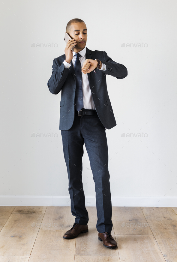 Businessman talking on call checking time fro wrist watch - Stock Photo - Images