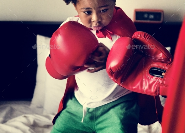 African descent kid wearing robe doing boxing with dad on the bed - Stock Photo - Images