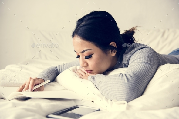Asian woman lying on bed - Stock Photo - Images
