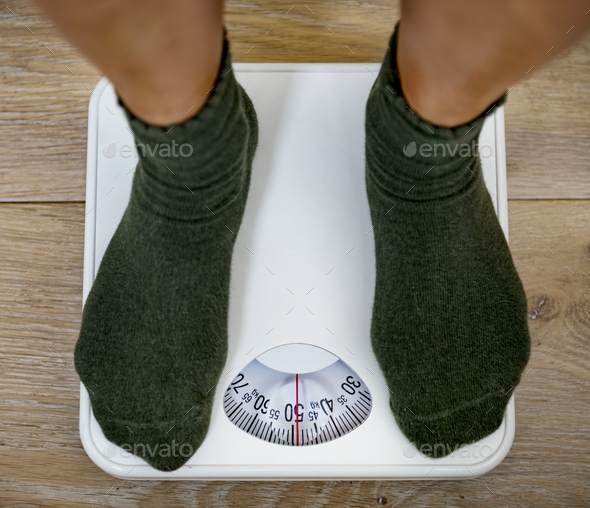 Woman on a weight scale - Stock Photo - Images
