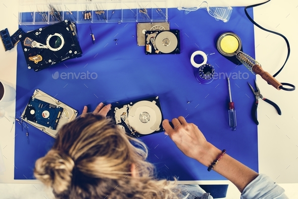 Caucasian technician fixing HDD at workstation - Stock Photo - Images