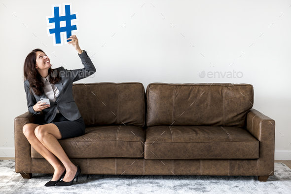 Businesswoman sitting on couch holding icon - Stock Photo - Images