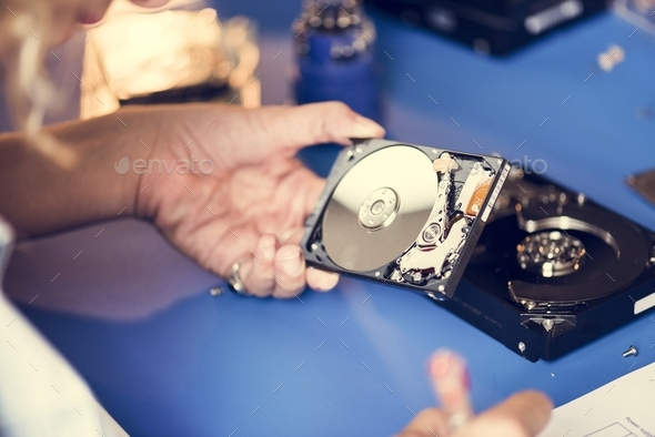 Hand hold HDD to fix at workshop station - Stock Photo - Images