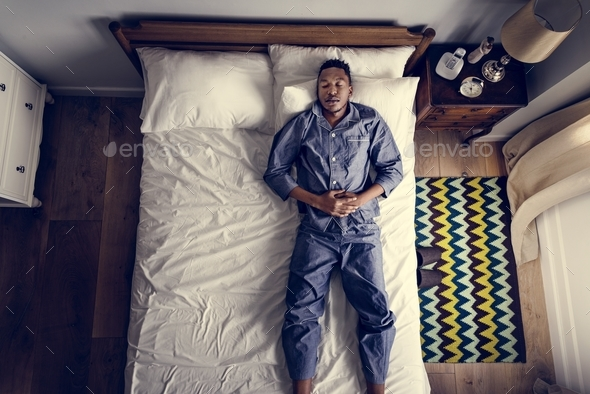Lonely man sleeping alone on the bed - Stock Photo - Images