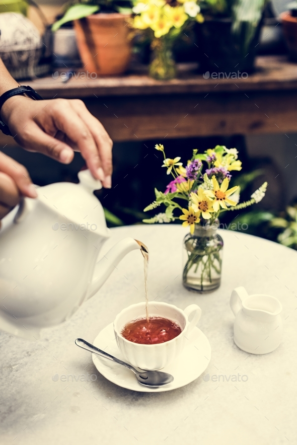 Woman pouring tea in a cup - Stock Photo - Images