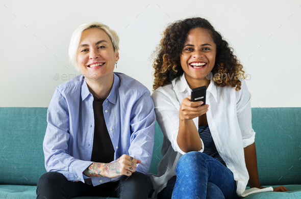 Girls sitting on the couch watching tv - Stock Photo - Images