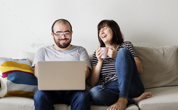 Couple using laptop together on the couch - Stock Photo - Images