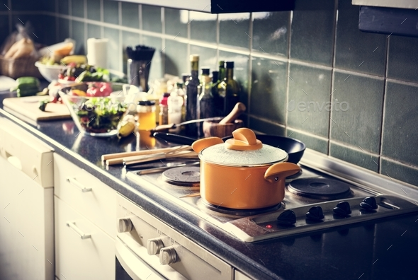 Closeup of pot on stove in the kitchen with cooking food - Stock Photo - Images