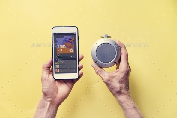 Hands holding smartphone connect to bluetooth speaker - Stock Photo - Images
