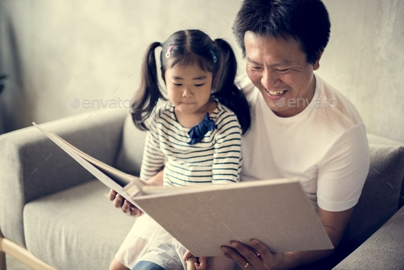 Asian father and daughter reading together - Stock Photo - Images
