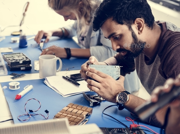 Electrical technicians working on electronics parts - Stock Photo - Images