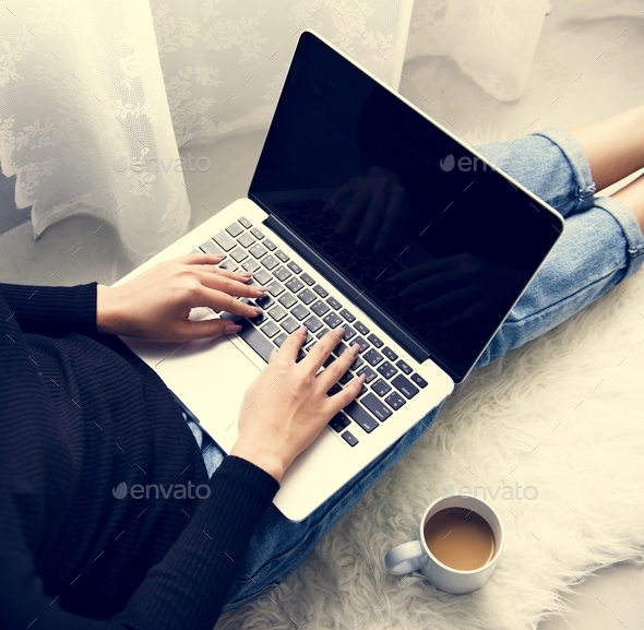 Woman sitting on the floor and using laptop - Stock Photo - Images