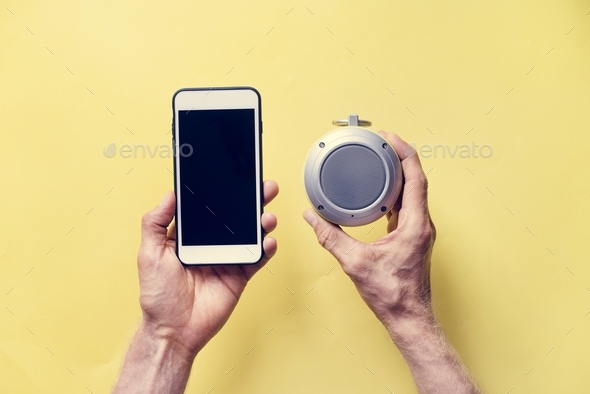 Hands holding smartphone and bluetooth speaker - Stock Photo - Images