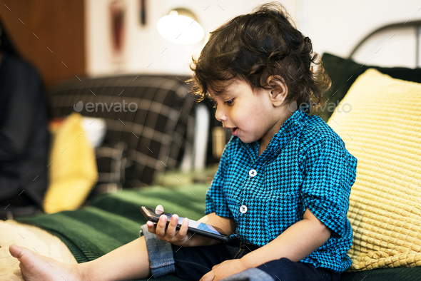 Young Indian boy using mobile phone - Stock Photo - Images