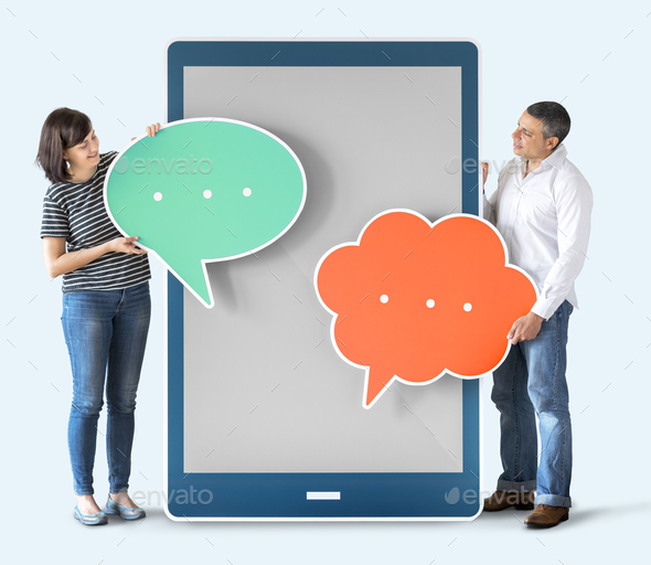 Diverse people holding speech bubbles and tablet - Stock Photo - Images