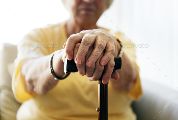 Senior woman holding a walking stick - Stock Photo - Images