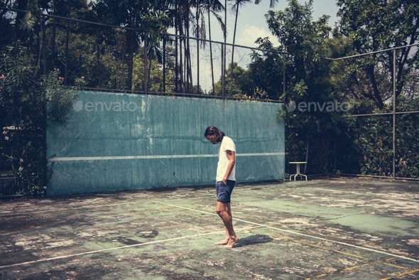 Man standing in a tennis court - Stock Photo - Images