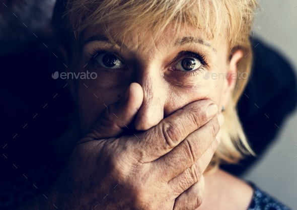 Closeup of caucasian woman with a hand covering her mouth - Stock Photo - Images