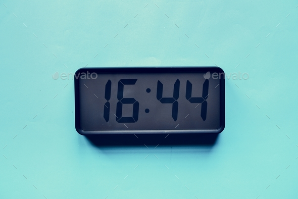 Digital clock on blue background - Stock Photo - Images