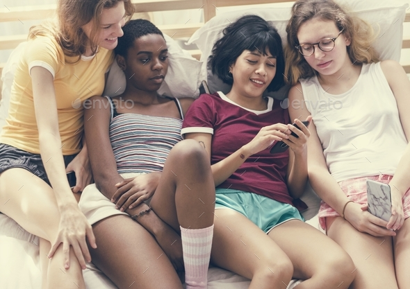 A group of diverse women lying on bed and using mobile phones - Stock Photo - Images