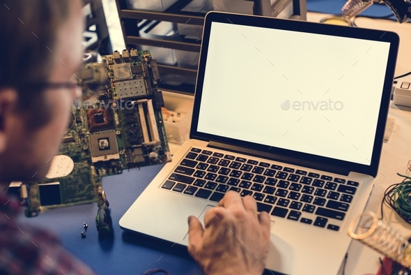 Technician man working on laptop with mockup screen - Stock Photo - Images