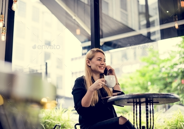 A young woman drinking coffee and making a phone call - Stock Photo - Images