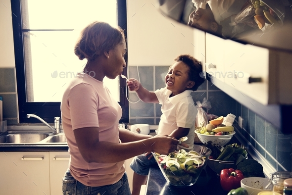 Kid feeding mom in the kitchen - Stock Photo - Images