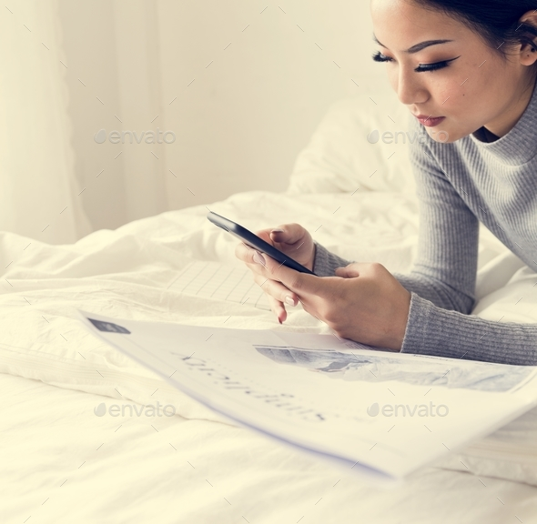 Asian woman lying on bed using mobile phone - Stock Photo - Images