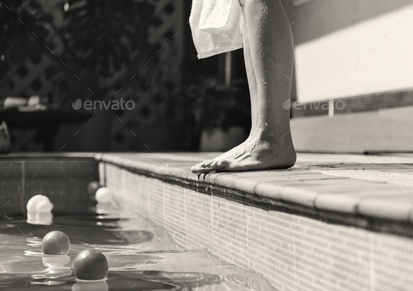 Woman standing by a swimming pool - Stock Photo - Images