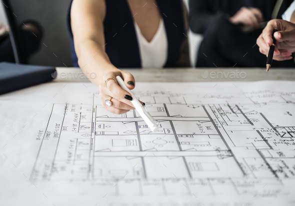Woman pointing at building plan - Stock Photo - Images