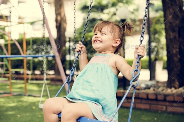 Little girl having fun playing in the park - Stock Photo - Images