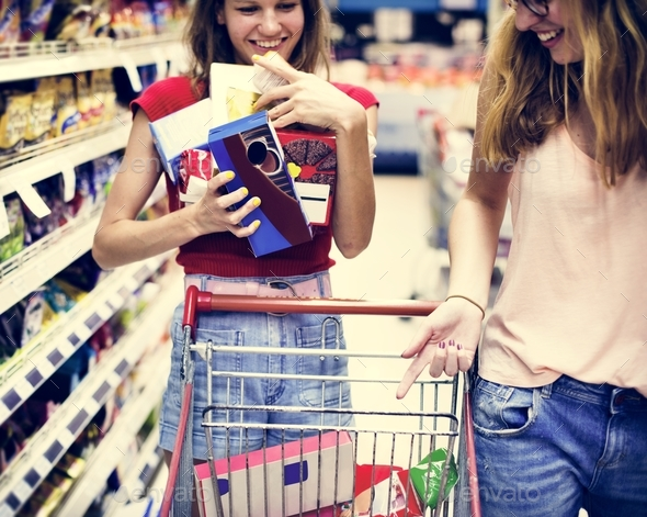 Women choosing food from a supermarket shelf - Stock Photo - Images