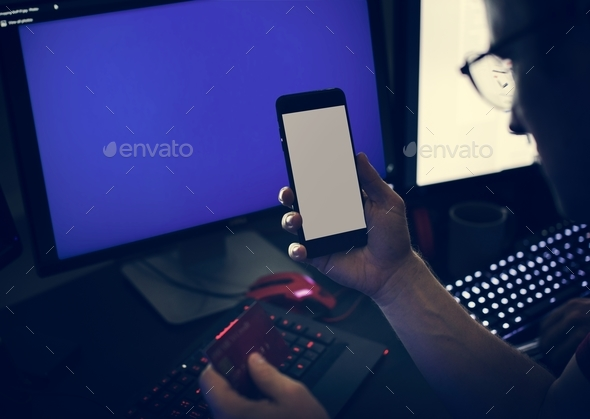 Closeup of hands holding mobile phone with computer laptop background - Stock Photo - Images