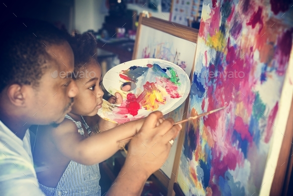 African descent dad teaching his child how to paint - Stock Photo - Images