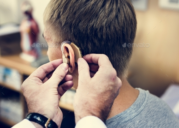 A man having his ears checked - Stock Photo - Images