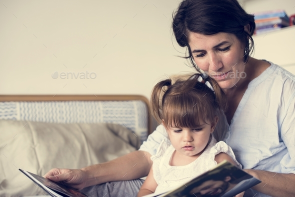 Mother and daughter looking photo album together - Stock Photo - Images