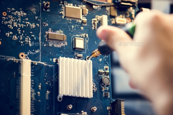Closeup of hands with screwdriver over computer mainboard - Stock Photo - Images
